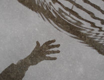Hand in rainy day. Picture of shadow of the hand on sidewalk on rainy day Royalty Free Stock Images