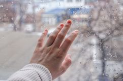 A hand on a rainy window royalty free stock photography