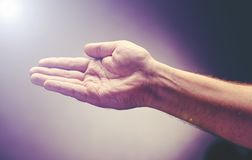 Hand raise with the palm opened up. Worship or pray for good things under the light ray from heaven Stock Photography