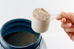 The hand raise a spoon measure Whey protein chocolate powder for Stock Photo