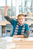 Hand raised - male student in classroom. With books Royalty Free Stock Photography