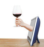 Hand raising big glass with red wine leans out TV Stock Image