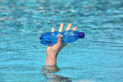 Hand raising out of water holding plastic blue bottle of water. Close up Royalty Free Stock Image