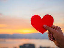 Hand is raising the red paper heart with blur sunlight during sunset, Stock Photography