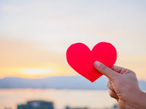 Hand is raising the red paper heart with blur sunlight during sunset, Royalty Free Stock Photos