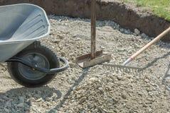 Wheelbarrow, hand compressor and rake at road construction royalty free stock image