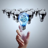 Hand reach 3d metal brain inside  light bulb. Of leadership concept Royalty Free Stock Photography