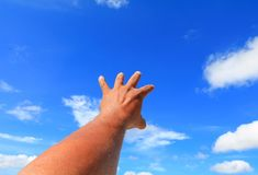 Hand reach out so it the on  blue sky background.  Royalty Free Stock Images