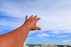 Hand reach up blue sky background.  Stock Image