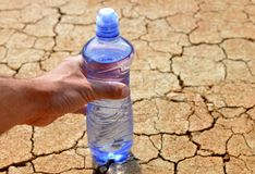 Hand reaches a bottle of water on dry cracked soil. Royalty Free Stock Image