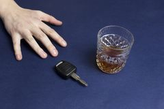 Hand reaches for car key and alcohol drive royalty free stock photo