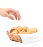 Hand reaches for the croissants in a basket. Stock Photo