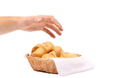Hand reaches for the croissants in a basket. Royalty Free Stock Photos