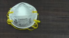Hand Reaches for an N95 Respirator Dust Mask from a Stack