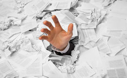 Hand reaches out from crumpled papers. Hand reaches out from big heap of crumpled papers Stock Photos