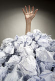 Hand reaches out from heap of papers. Hand reaches out from big heap of crumpled papers Stock Image