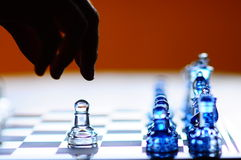 Hand Reaches for Strategically Lonely Glass Chess Royalty Free Stock Photo