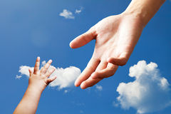 Hand reaching. Child hand and adult hand reach each other Stock Photos