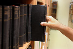 Hand reaching for book on a shelf stock image