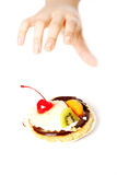 Hand reaching for a cake. Royalty Free Stock Photo