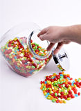 Hand reaching into candy jar. Hand reaching into open jar of jelly beans with silver lid and pile of colorful candy Royalty Free Stock Image