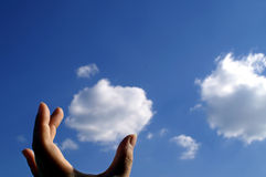 Catching clouds and dreams. Hand reaching for clouds - can be used for environmental subjects or simply to illustrate reaching for goals, dreams or ideas Stock Image