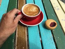 Hand reaching for a delicious cup of cappuccino. Biscuit and a red cup with coffee latte captured in a restaurant on a colorful table Royalty Free Stock Photo