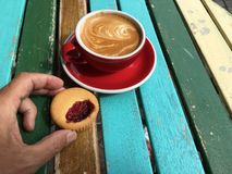 Hand reaching for a delicious cup of cappuccino. Biscuit and a red cup with coffee latte captured in a restaurant on a colorful table Stock Image
