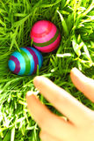 Hand reaching for Easter eggs Stock Photo
