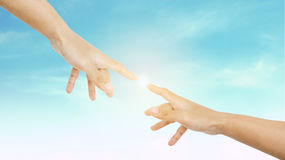 Hand reaching finger together with shine bright light, on sky background Royalty Free Stock Image
