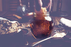 Hand reaching honeycomb from jar of healthy real honey and fruit Stock Photography