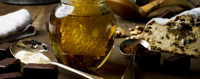 Hand reaching honeycomb from jar of healthy real honey and fruit Royalty Free Stock Photography