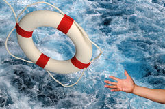 Hand reaching for Lifering. Hand reaching for life ring over churning waters stock image