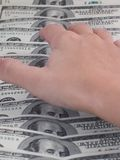 Hand reaching for money. Hand reaching for dollars banknotes Royalty Free Stock Photo