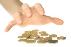 Hand reaching for money. Male hand reaching greedily for some Euro coins royalty free stock image
