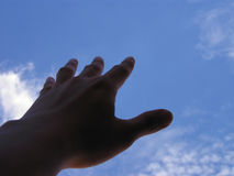 Hand reaching out. Silhoutted hand reaching out from the dark towards the sky. Focus on hand royalty free stock image