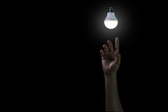 Hand reaching out to light in black. Hopeful concept Stock Image