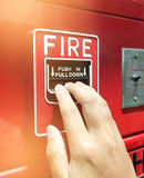 A hand reaching and pulling a red fire alarm switch. red fire alarm. Push in pull down Royalty Free Stock Photography