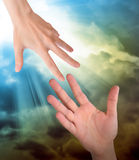 Hand Reaching for Safety Help in Clouds. A hand is reaching out or grabbing for help from another hand in the sky. Clouds are in the sky as the background. Use stock photography