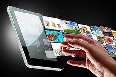 Hand reaching streaming multimedia of the tablet. Multimedia streaming of the tablet screen with reaching hand. All images coming from my gallery Stock Images