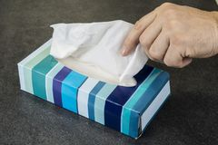 Hand is reaching for the tissue in the box.  royalty free stock photo