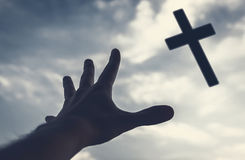 Hand reaching to the cross in the sky. Hand of a man reaching to the cross in the sky. Color toned image Royalty Free Stock Photography