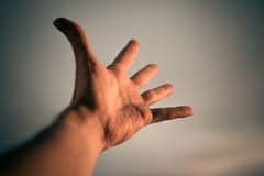 Hand reaching to sky. Hand of a man reaching to towards sky. Color toned image. Selective focus Royalty Free Stock Photo