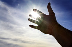 Hand Reaching Towards the Light of Heaven Seeking Help Royalty Free Stock Photography