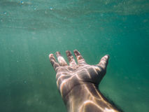 Hand reaching underwater. Hand outstretched under water with bubbles Royalty Free Stock Photo