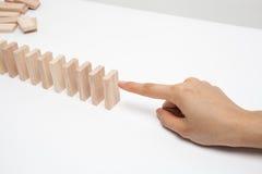 Hand ready to push domino . Royalty Free Stock Photo