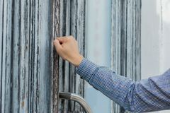 Hand realtor in a plaid shirt knocking his fist at the old and shabby front door. Anybody home stock images