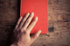 Hand on a red book Stock Photo