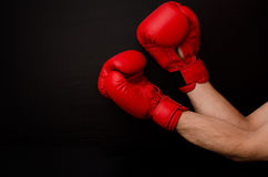 Hand in red boxing gloves in the corner of the frame on a black background, empty space Royalty Free Stock Images