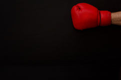 Hand in red boxing gloves in the corner of the frame on a black background, empty space, vertical Stock Photos